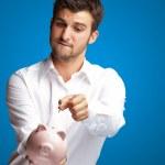 un uomo d'affari, mettendo una moneta in un rosa salvadanaio — Foto Stock