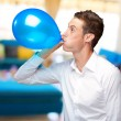 Portrait Of Young Man Blowing A Balloon — Stock Photo
