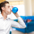 Portrait Of Young Man Blowing Balloon — Stock Photo #11959694
