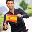 Photo: Portrait of a young man holding a flag