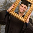 Graduate man looking through a frame — Stock fotografie