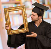 Graduate man showing a frame — Stock Photo