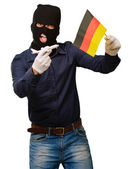 Man wearing a robber mask and holding airplane miniature and fla — Foto Stock