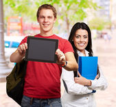 Students holding tablet and books — Stock Photo
