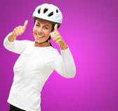 Mujer vestida con pulgar casco mostrando arriba — Foto de Stock