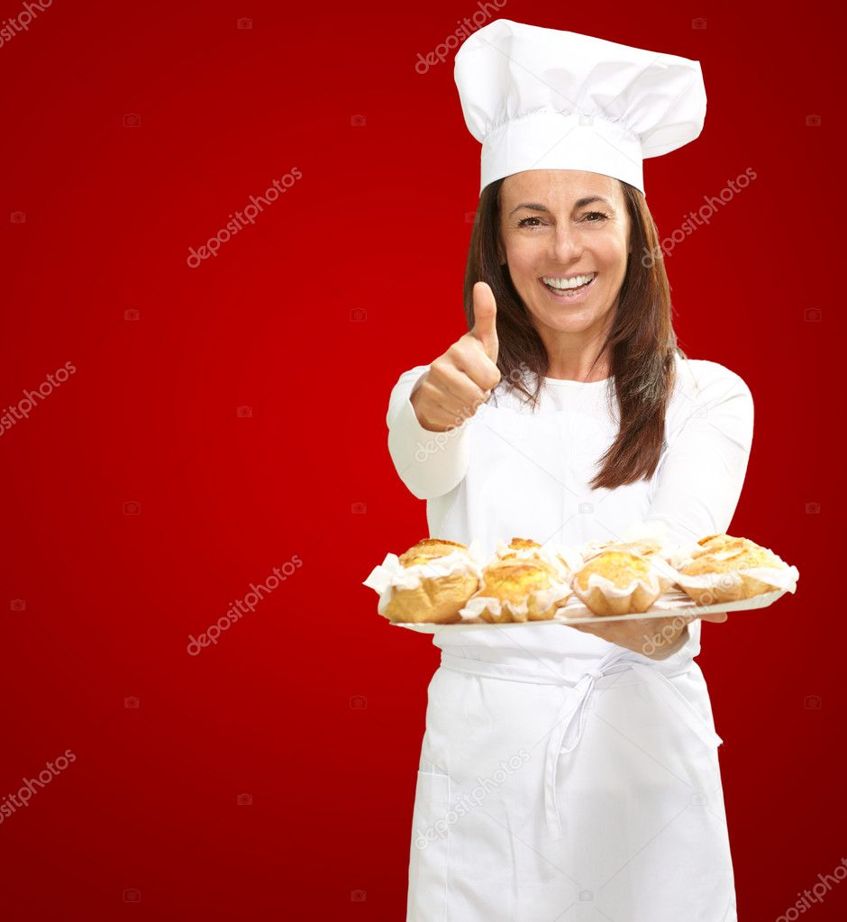 Woman chef holding baked food on red background  Stock Photo #11990743