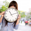 Stock Photo: Woman Holding Clock Winking