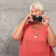 Senior Woman Holding Camera - Stock Photo