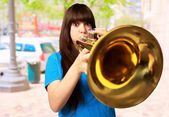 Portrait of a young girl blowing trumpet — Photo