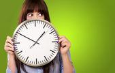 一个年轻的女孩举行一个时钟 — 图库照片