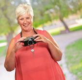 Senior Woman Holding Camera — Stockfoto