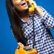 Portrait of young woman talking on vintage telephone over blue — Stock Photo
