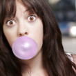 Young girl with a pink bubble of chewing gum against a street ba — Stock Photo #12093484