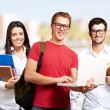 Group of young students against a university — Stock Photo