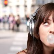 Portrait of young woman listening to music with bubble gum again — Stock Photo