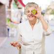 Stock Photo: Portrait of senior woman holding kiwi in front of her eye at str