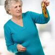 Senior woman holding a rotten banana indoor - Stock Photo