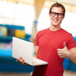 Man holding laptop with thumbs up — Stock Photo