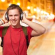 Portrait of cheerful young student listening music with headphon — Stock Photo #12094001