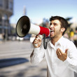 Portrait of young man shouting with megaphone at street — Stock Photo
