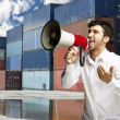 Portrait of young man shouting with megaphone at harbor — Stock Photo