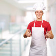 Portrait of young cook man doing success symbol at entrance of m — Stock Photo