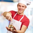 Photo: Portrait of young cook man pressing a golden bell indoor