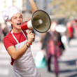 Portrait of young cook man shouting with megaphone at crowded st — Stock Photo #12094153