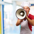 Portrait of young cook man screaming with megaphone indoor — Stock Photo #12094157