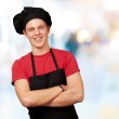 Portrait of young cook man wearing uniform and smiling against a — Stock Photo #12094176