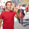 Portrait of young man eating pizza portion at crowded street — Stock Photo