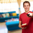 Portrait of a young man holding popcorn — Stock Photo