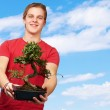 Stock Photo: Portrait of a young man holding a pot