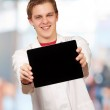 Portrait of young man showing digital tablet indoor — Stock Photo #12094265