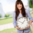 Stock Photo: A Young Girl Holding A Clock