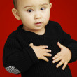 Portrait of adorable kid touching his stomach against a red back — Stock Photo
