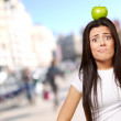 Portrait of young woman holding green apple on her head at crowd — Stock Photo #12095030