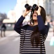 Portrait of young girl looking through a binoculars at city — Stock Photo #12095152