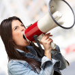 Portrait of young woman screaming with megaphone indoor — Stock Photo #12095172