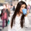 Portrait of young woman drinking at crowded city — Stock Photo #12095193