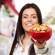 Portrait of young woman offering cereals bowl at street — Stock Photo #12095203