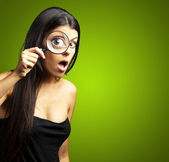 Portrait of young woman surprised looking through a magnifying g — Stock Photo