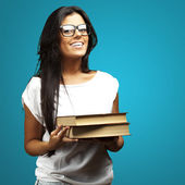 Portrait of young girl holding books over blue background — Stock Photo