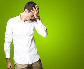 Angry young man doing frustration gesture over green background — Stock Photo