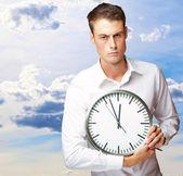 Hombre enojado que sostiene un reloj — Foto de Stock