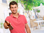Young man holding a beer — Stock Photo