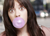 Young girl with a pink bubble of chewing gum against a street ba — Stock Photo