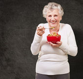 Portrait of senior woman holding a cereals bowl against a grunge — Stock Photo