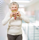Portrait of senior woman eating vegetal sandwich at modern place — Foto de Stock