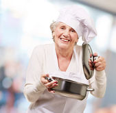 Portrait of cook senior woman opening sauce pan indoor — Stock Photo